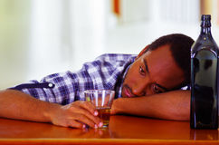 Handsome man wearing white blue shirt sitting by bar counter lying over desk drunk sleeping, alcoholic concept Stock Images