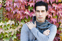 Handsome man wearing winter clothes in autumn leaves background Stock Images