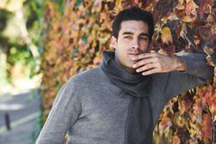 Handsome man wearing winter clothes in wooden background. Royalty Free Stock Photography