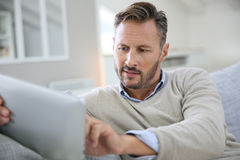 Handsome man websurfing on tablet Royalty Free Stock Images