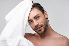 Handsome man with wet hair and towel. Isolated on grey stock images