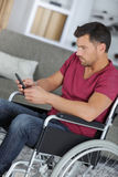 Handsome man in wheelchair texting on phone Royalty Free Stock Image