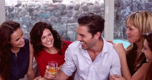 Handsome man with whiskey discussing with women