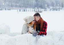 The handsome man is whispering something funny in the ear of his laughing girlfriend. Winter village location. The handsome men is whispering something funny in Stock Photos