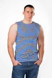 Handsome man on white. Muscular man in a striped vest, in casual clothes posing on light background. strength, fitness, fashion, health, muscles. Young strong Royalty Free Stock Images