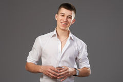 Handsome man in white shirt with glass of water. On grey bakground Stock Images