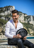 Handsome man in white shirt and hat on beach Stock Photography