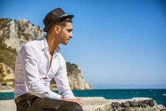 Handsome man in white shirt and hat on beach Royalty Free Stock Photo
