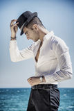 Handsome man in white shirt and hat on beach. Young handsome man in elegant white shirt and black fedora hat, on beach while looking away. Sea waves on Royalty Free Stock Images