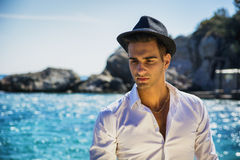 Handsome man in white shirt and hat on beach. Young handsome man in elegant white shirt and black fedora hat, on beach while looking away. Sea waves on Stock Photo