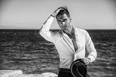 Handsome man in white shirt and hat on beach. Young handsome man in elegant white shirt and black fedora hat, on beach while looking away. Sea waves on Stock Images