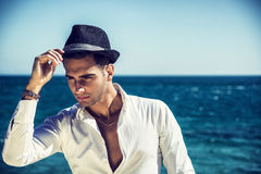 Handsome man in white shirt and hat on beach. Young handsome man in elegant white shirt and black fedora hat, on beach while looking away. Sea waves on Stock Image