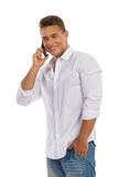 Handsome Man In A White Shirt On The Phone. Handsome smiling young man in white unbuttoned shirt ans jeans shorts standing relaxed with hand in pocket and Royalty Free Stock Image