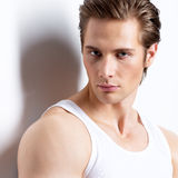 Handsome man in white shirt poses at studio. Stock Images