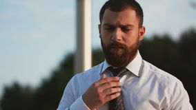 Handsome man in white shirt tying the necktie outdoors stock video