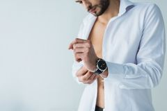 Handsome man in white shirt wearing wristwatch,. Isolated on grey Stock Photography