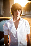 Handsome man in white and sunglasses posing near car Royalty Free Stock Photography
