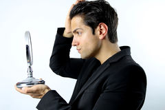 Handsome man who admires her face in a mirror Royalty Free Stock Photography