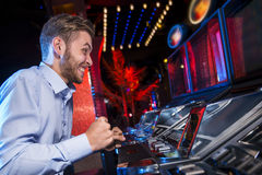 Handsome man winning at the slot machine Stock Image