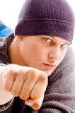 Handsome man with winter cap showing fist. On an isolated background Royalty Free Stock Photography