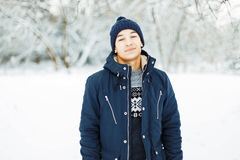 Handsome man in a winter jacket and a sweater walks. Beautiful snowy winter day royalty free stock image
