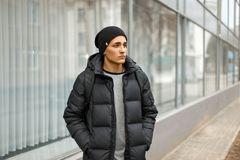 Handsome man in winter warm jacket with a backpack walking Royalty Free Stock Images