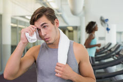 Handsome man wiping his forehead beside treadmills Stock Images