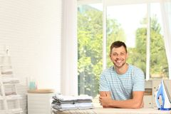 Free Handsome Man With Iron And Clean Laundry Near Board At Home Royalty Free Stock Photos - 161048678
