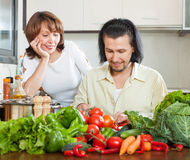 Handsome man and woman with vegetables in the kitchen Stock Photos