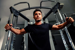 Handsome man work out in gym on trainer Stock Images