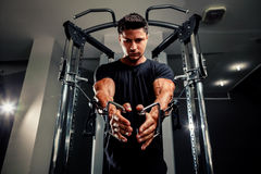 Handsome man work out in gym on trainer Stock Photos