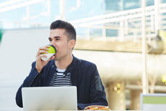 Handsome man working at cafe on laptop drinking coffee Royalty Free Stock Photo
