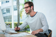 Handsome man working on computer and taking notes Royalty Free Stock Image