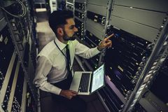 Man in data centre. Handsome man is working in data centre with laptop.IT engineer specialist in network server room.Running diagnostics and maintenance royalty free stock image