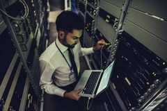 Man in data centre. Handsome man is working in data centre with laptop.IT engineer specialist in network server room.Running diagnostics and maintenance royalty free stock images