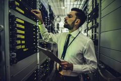 Man in data centre. Handsome man is working in data centre with tablet.IT engineer specialist in network server room.Running diagnostics and maintenance stock photos