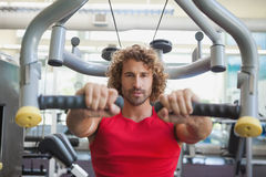 Handsome man working on fitness machine at gym Royalty Free Stock Photography