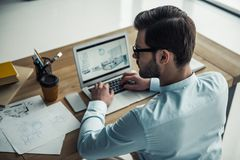 Handsome man working. Handsome interior designer in eyeglasses is working with the laptop in the office Royalty Free Stock Images