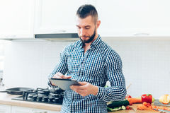 Handsome man working in kitchen, looking up on the internet receipes. Details of modern cook working with tablet Royalty Free Stock Image