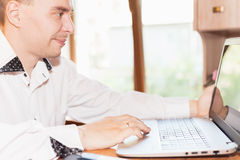 Handsome man working at laptop at home remotely Royalty Free Stock Photo