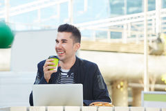 Handsome man working on laptop at outdoor cafe with coffee Royalty Free Stock Photos