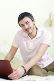 Handsome man working online on laptop from home Stock Image