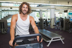 Handsome man working out on exercise bike at gym Royalty Free Stock Images