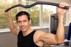 Handsome man working out in a gym Stock Images