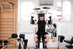 Handsome man working out at gym, daily chest exercise routine Stock Image
