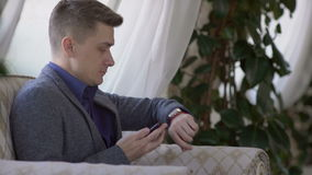 Handsome man working with smartphone and documents