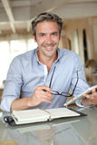 Handsome man working on tablet at home Stock Images