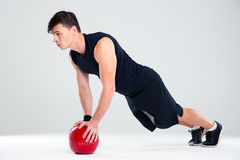 Handsome man workout with fitness ball. Full length portrait of a handsome man workout with fitness ball isolated on a white background Royalty Free Stock Photos