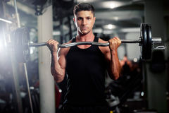Handsome man workout in gym. Handsome athletic man workout in gym with weights Stock Photography
