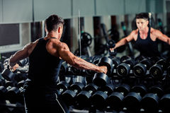 Handsome man workout in gym. Handsome athletic man workout in gym with weights Stock Images